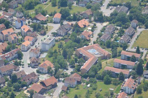 Luftaufnahme des Dorfzentrums Bettlach mit dem markanten Altersheimbau mit verglastem Innenatrium.